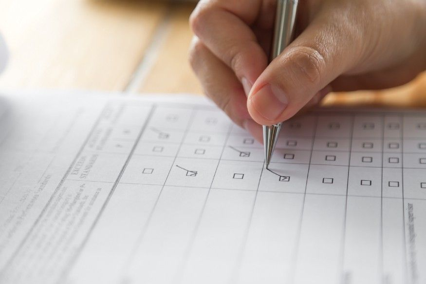 A photograph of a person filling up a form that has checkboxes.